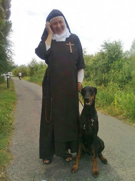 traditional nun with doberman dog